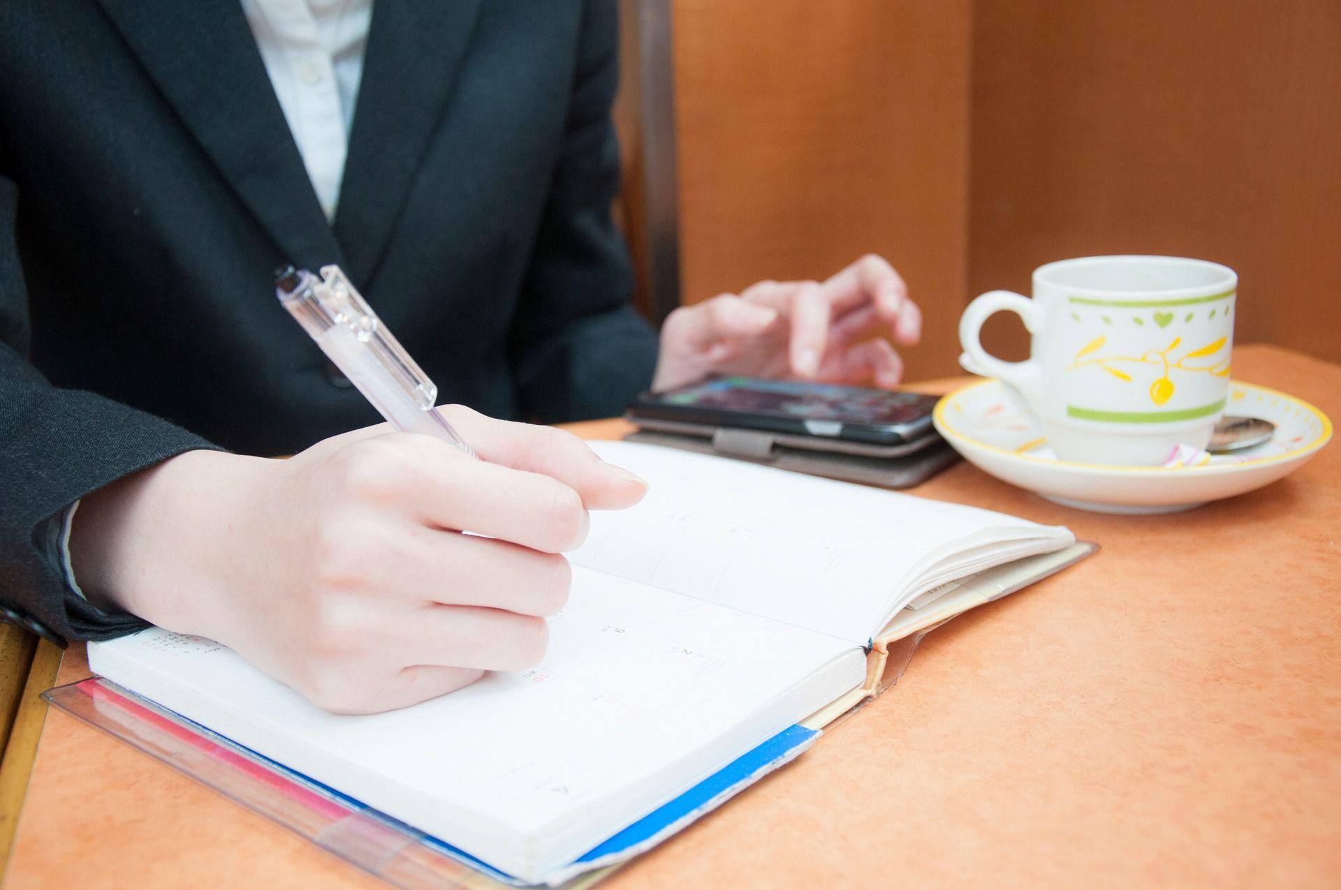 仕事の合間にスマホを使ってカフェで勉強する女性